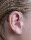 image of a person wearing a behind the ear hearing aid